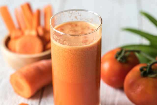 tomatoes and carrot juice on highball glass
