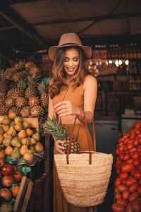 woman putting pineapple in bag